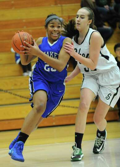 Shaker's Lyrc Artis is guarded by Shenendehowa's Carly Boland as she drives to the hoop during a bas