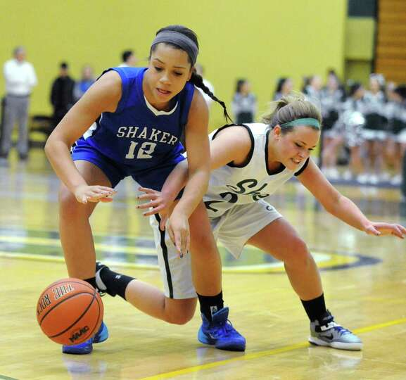 Shaker's Merrick Rowland and Shenendehowa's Ashley Acker battle for the ball during a basketball gam
