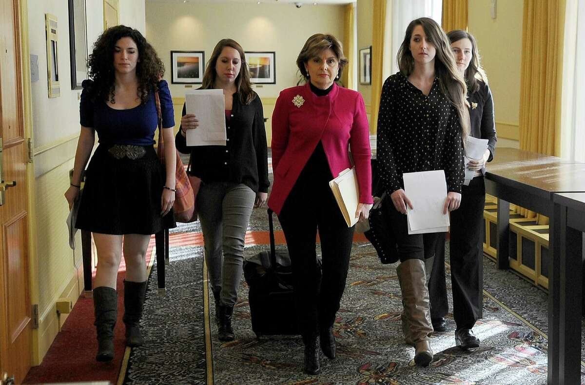Attorney Gloria Allred, center, walks with University of Connecticut students Rose Richi, left, Erica Daniels, Carolyn Luby, second from right, and Kylie Angell, right, to a news conference in Monday, Oct. 21, 2013, in Hartford, Conn. Four women who say they were victims of sexual assaults while students at the University of Connecticut have announced they are filing a federal discrimination lawsuit against the school.