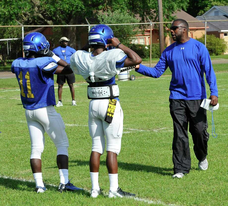 New Head Coach Keeath Magee, right, gives ball handling instructions to some of his players including quarterback Jarvaris Curl, center.  Monday afternoon, April 29, 2013, was the first day of spring football practice for the Ozen football team under the direction of new head coach Keeath Magee.    Dave Ryan/The Enterprise Photo: Dave Ryan