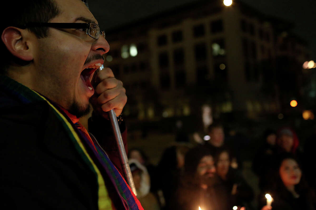 """Supporters of marriage equality including Julius Lorenzi, left, chant during the """"Light The Path to Marriage Equality"""" candlelight vigil outside the Bexar County Courthouse in San Antonio on Tuesday, Feb. 11, 2014."""