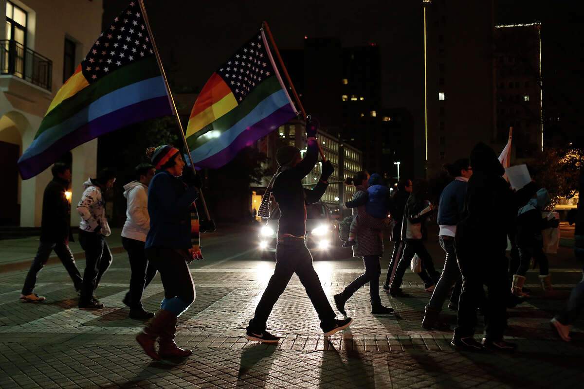 """Supporters of marriage equality cross Commerce Street during the """"Light The Path to Marriage Equality"""" march from Milam Park to the Bexar County Courthouse in San Antonio on Tuesday, Feb. 11, 2014."""