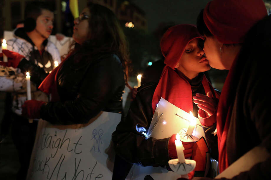 "Noel Bonham, 10, kisses his mother, Amy Bonham, during the ""Light The Path to Marriage Equality"" candlelight vigil in San Antonio on Tuesday, Feb. 11, 2014. Supporters of marriage equality marched from Milam Park to the Bexar County Courthouse during the event organized by GetEQUAL Texas. Noel's sister, Felicia Quintanilla, left, is gay and hopes to be able to marry her partner when the time comes. Photo: Lisa Krantz / San Antonio Express-News"