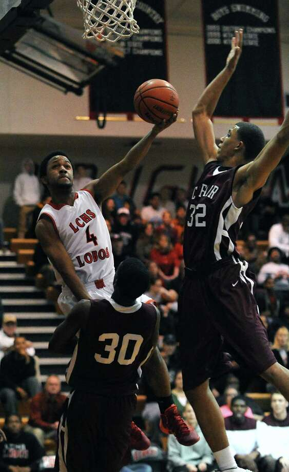 Langham Creek's Dvon England (4) drives against Cy-Fair's Nuerri Butler, left, and Bryson Lockley. Photo: Eric Christian Smith, Freelance