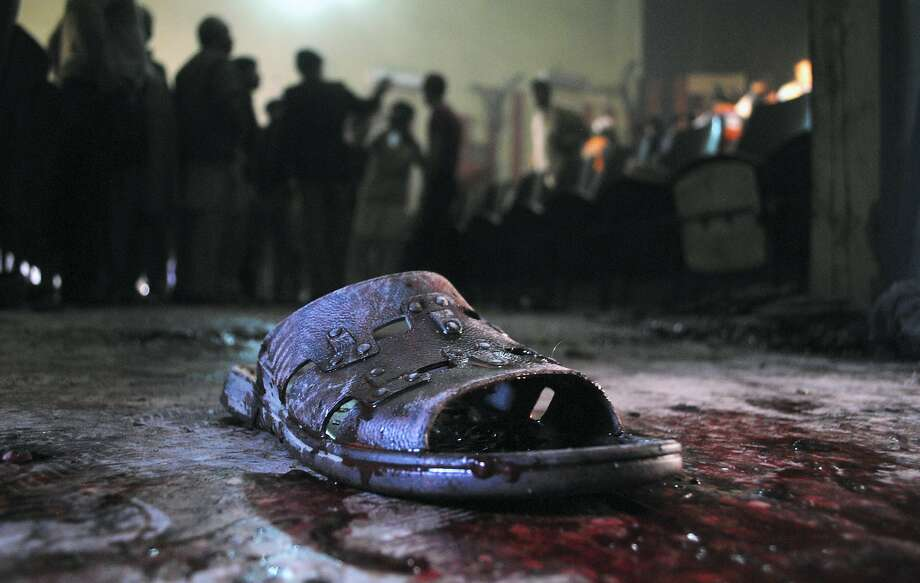 "A blood-stained shoe of a victim lies on the ground at the site of a grenade attack on a crowded movie theater that killed and wounded many people in Peshawar, Pakistan, Tuesday, Feb. 11, 2014. About 80 people were watching a movie called ""Yarana,"" which means friendship in Pashto, said an official. No one immediately claimed responsibility for the attacks, which come days after Pakistan began a peace process with Taliban militants fighting in the country's northwest to end the violence that has killed more than 40,000 people in recent years. (AP Photo/Mohammad Sajjad) Photo: Mohammad Sajjad, Associated Press"