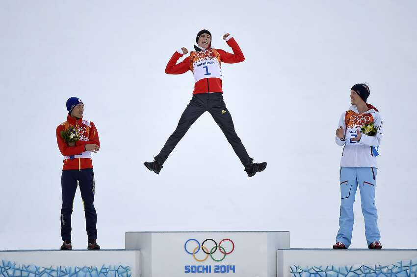 Gold medalist Eric Frenzel of Germany jumps in celebration alongside silver medalist Akito Watabe of Japan (L) and bronze medalist Magnus Krog of Norway (R) during the flower ceremony for the MenÂ's Nordic Combined Individual Gundersen Normal Hill and 10km Cross Country on day 5 of the Sochi 2014 Winter Olympics at the RusSki Gorki Nordic Combined Skiing Stadium on February 12, 2014 in Sochi, Russia.