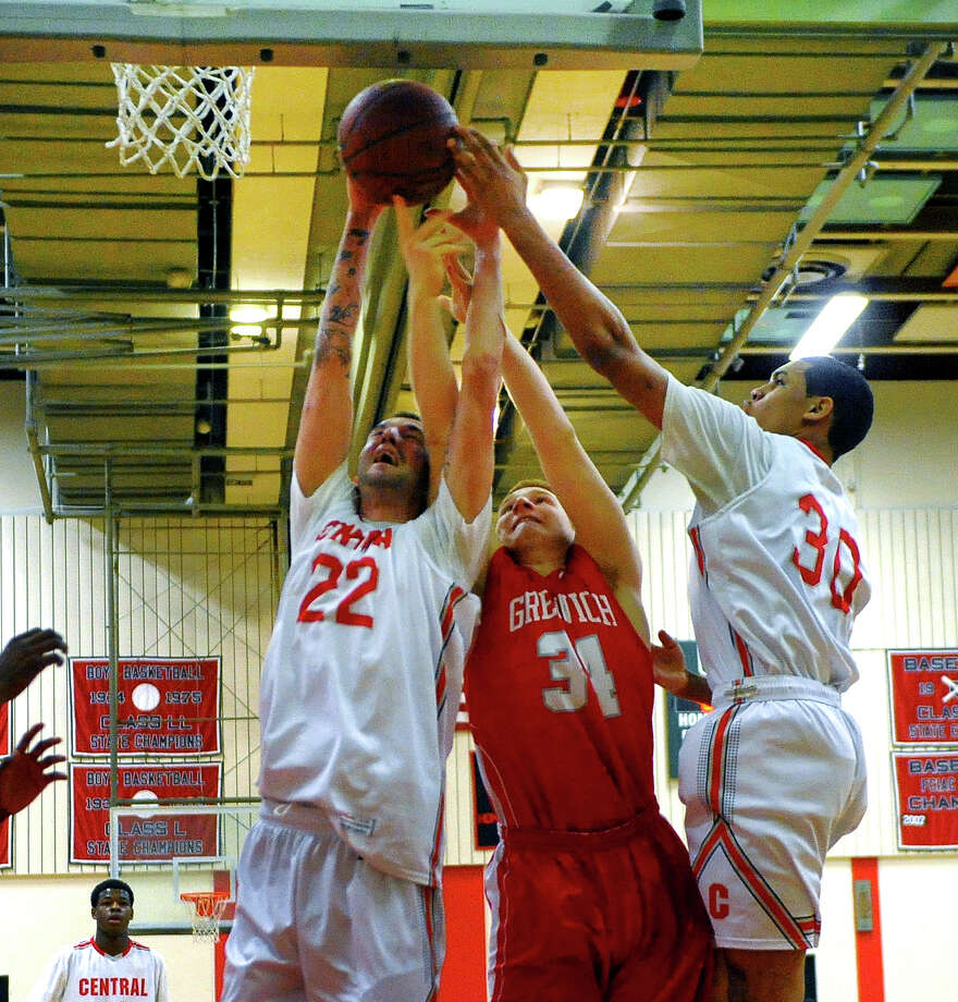 Greenwich's Griffin Golden, center and Central's Orhan Cecunjamin, left, and teammate Marcus Blackwell, right, reach for a rebound, during boys basketball action in Bridgeport, Conn. on Tuesday February 11, 2014. Photo: Christian Abraham / Connecticut Post