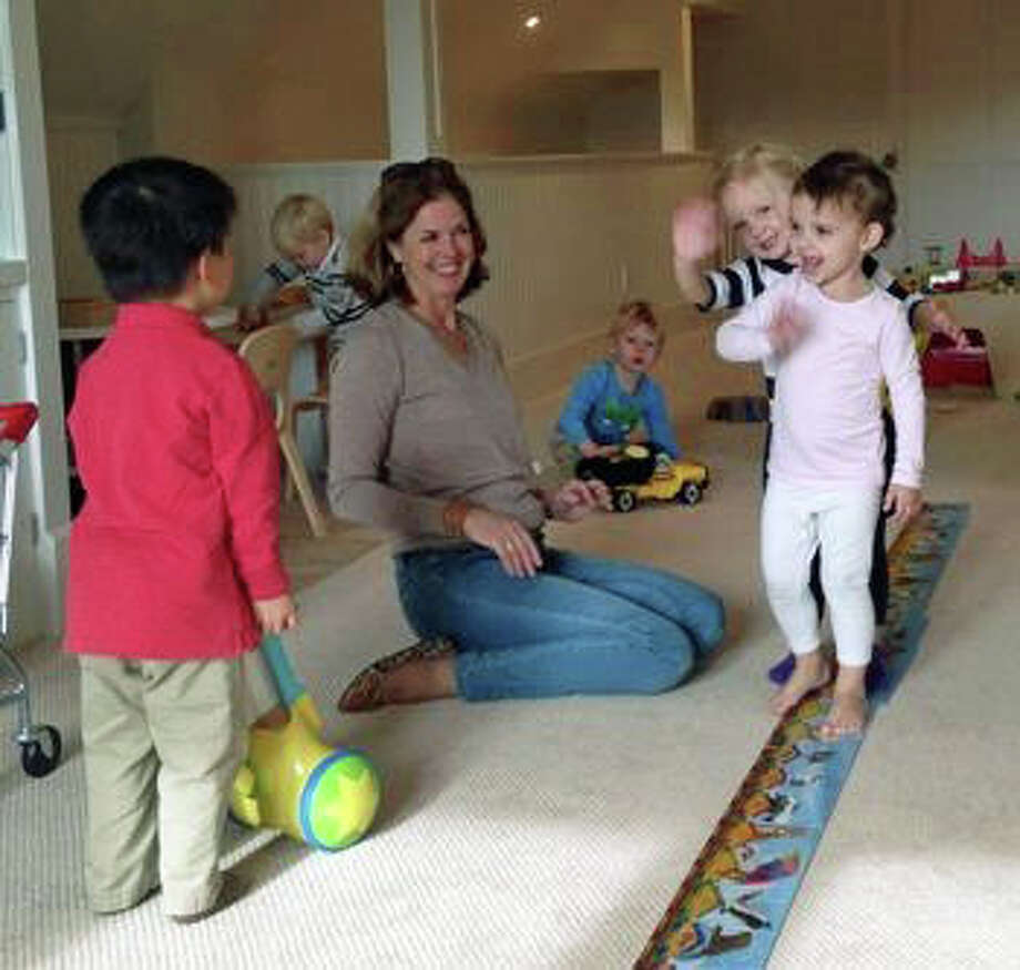With a rotating cycle of homes, there are always new toys and creative experiences to explore with Playdates. Josephine Andren and Merritt MacColl, of Darien, delight their teacher Mary Hayes by turning a puzzle into an impromptu balance beam. Photo: Contributed Photo, Contributed / Darien News