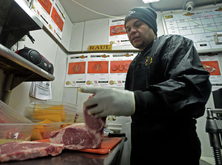 Raul Ipina slices up rib eyes Monday afternoon in the cooler at Texas Roadhouse. Ipina, who has been working at the Texas Roadhouse in Port Arthur for ten years, has advanced to the semi-finals of the National Meat Cutting Challenge. The competition is held between meat cutters employed by the steakhouse chain and has a grand prize of $20,000 and the title of Meat Cutter of the Year. Photo taken Monday, 2/10/14 Jake Daniels/@JakeD_in_SETX Photo: Jake Daniels / ©2013 The Beaumont Enterprise/Jake Daniels