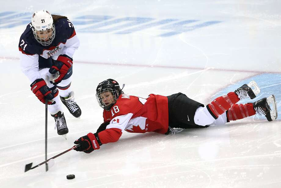 Hilary Knight #21 of the United States and Catherine Ward #18 of Canada go for a loose puck in the second period during the Women's Ice Hockey Preliminary Round Group A game on day five of the Sochi 2014 Winter Olympics at Shayba Arena on February 12, 2014 in Sochi, Russia. Photo: Bruce Bennett, Getty Images