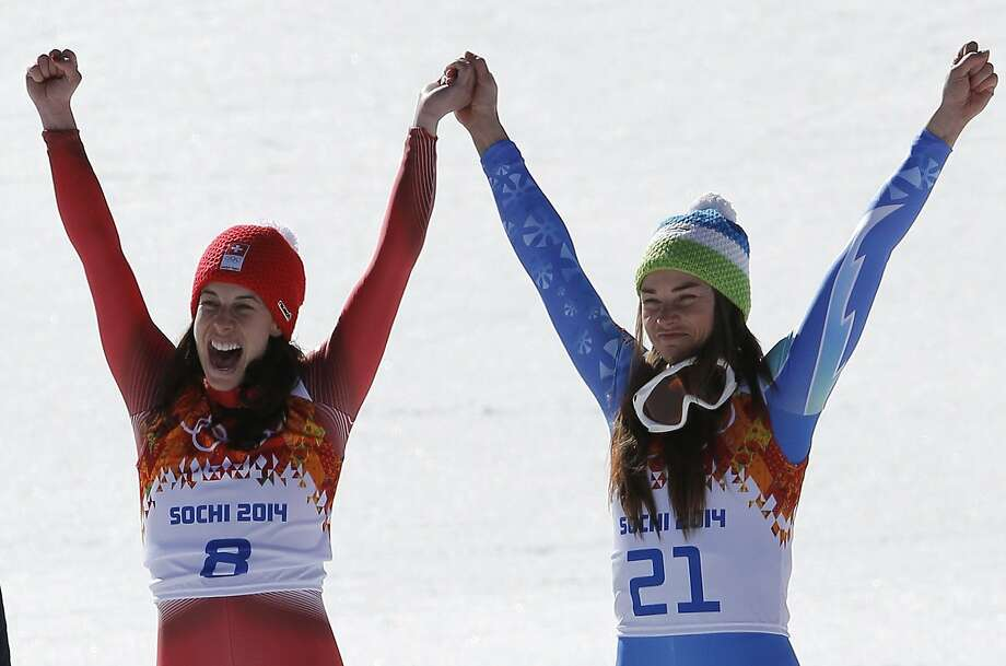 Women's downhill gold medalists Switzerland's Dominique Gisin, left, and Slovenia's Tina Maze, right, hold hands during a flower ceremony at the Sochi 2014 Winter Olympics, Wednesday, Feb. 12, 2014, in Krasnaya Polyana, Russia. Photo: Christophe Ena, Associated Press