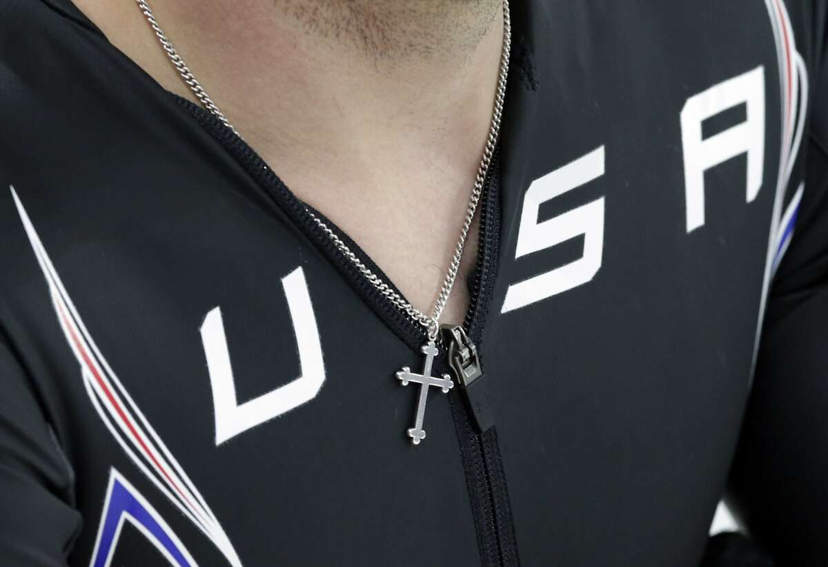 Jonathan Garcia of the U.S. wears a cross pendant and warms-up prior to the start of the men's 1000-meter speedskating race at the Adler Arena Skating Center during the 2014 Winter Olympics, Wednesday, Feb. 12, 2014, in Sochi, Russia. (AP Photo/Matt Dunham)