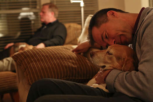 Victor Holmes, right, gives some love to one of their three beagles, Jake, while Mark Phariss sits with Betsy at their home in Plano on Friday, Feb. 7, 2014. Photo: Lisa Krantz, San Antonio Express-News / San Antonio Express-News
