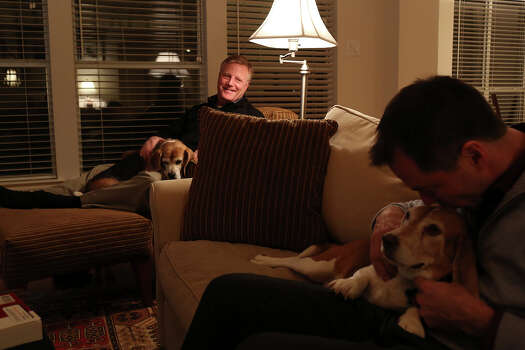 Mark Phariss, left, with Betsy, watches as Victor Holmes gives Jake some love at their home in Plano on Friday, Feb. 7, 2014. Photo: Lisa Krantz, San Antonio Express-News / San Antonio Express-News