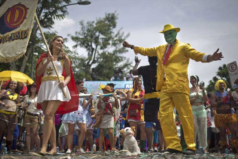A reveler dressed as superhero The Mask, shows off his moves in the 'Desliga da Justica' carnival block parade, a pre-Carnival celebration, in Rio de Janeiro, Brazil, Saturday, Jan. 26, 2013. According to Rio's tourism office, Rio's street Carnival this year will consist of 492 block parties gathering 5 million carnival enthusiasts and requiring authorities to set up 16,500 public toilets around the city. Only two weeks before Carnival official start, running this year from Feb. 9-12, Rio residents and tourists are certainly warming up. (AP Photo/Felipe Dana) Photo: Felipe Dana, Associated Press