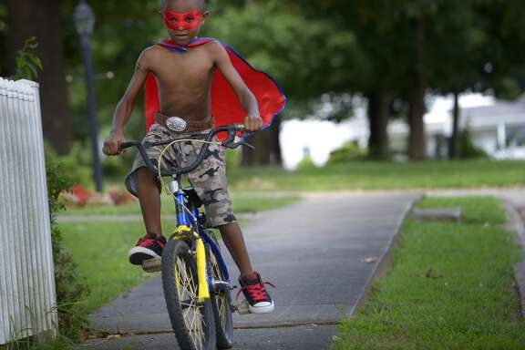 "Oziah Wright, 6, rides his bicycle down Climax Street in Graham, N.C. on the afternoon of Wednesday, July 24, 2013. When asked if he had a superhero name, he said that he refers to himself as ""Cyclon."" (AP Photo/Burlington Times-News, Scott Muthersbaugh)"