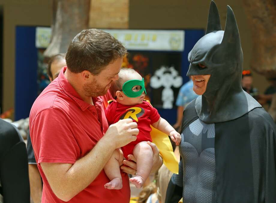 061613 ATLANTA: -- WHO IS THAT MASKED MAN? - David Carney, Sandy Springs, Ga.,  introduces his 6-month-old son Jackson, dressed up like Robin, to Batman during Superhero Day 2013 at Fernbank Museum of Natural History on Sunday, June 16, 2013, in Atlanta. The annual event helps celebrate super dads on Fathers Day. Carney said it was his fourth year attending the event with his family that features a costume contest, mini hero craft, and costumed characters.        (AP Photo/Atlanta Journal-Constitution, Curtis Compton)  MARIETTA DAILY OUT; GWINNETT DAILY POST OUT; LOCAL TV OUT; WXIA-TV OUT; WGCL-TV OUT Photo: CURTIS COMPTON, Associated Press