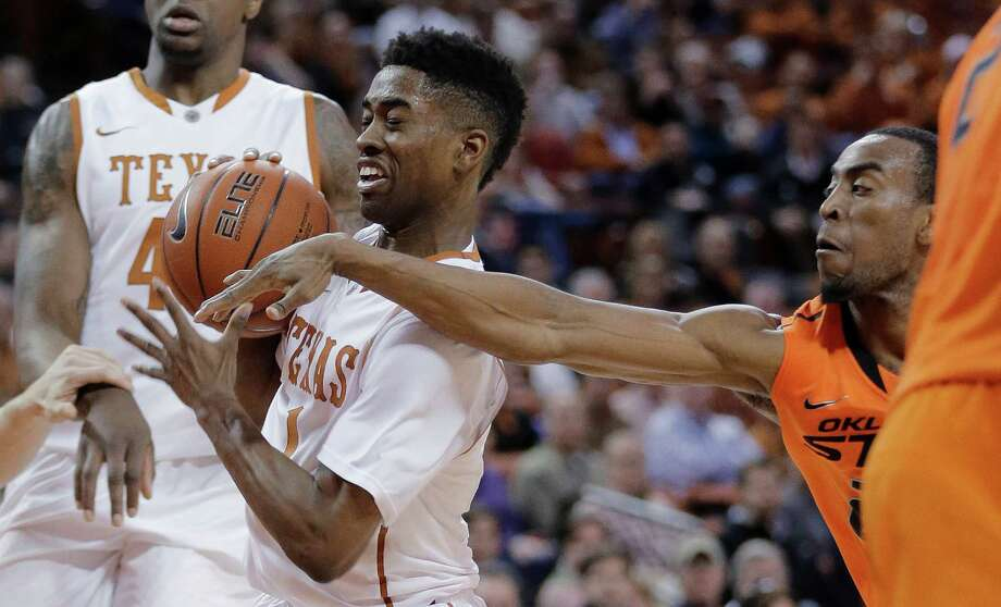 Texas' Isaiah Taylor (1) tries to protect the ball from Oklahoma State's Markel Brown during the first half on an NCAA college basketball game, Tuesday, Feb. 11, 2014, in Austin, Texas. (AP Photo/Eric Gay) Photo: Eric Gay, Associated Press / AP