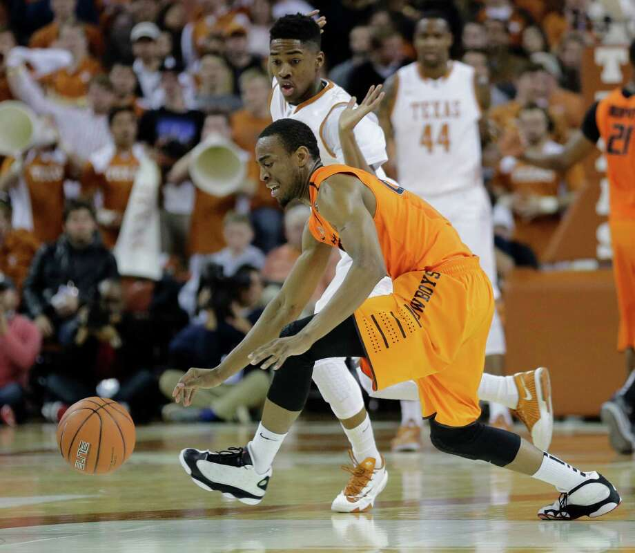 Oklahoma State's Markel Brown (22) is pressured by Texas' Isaiah Taylor (1) during the first half on an NCAA college basketball game, Tuesday, Feb. 11, 2014, in Austin, Texas. (AP Photo/Eric Gay) Photo: Eric Gay, Associated Press / AP