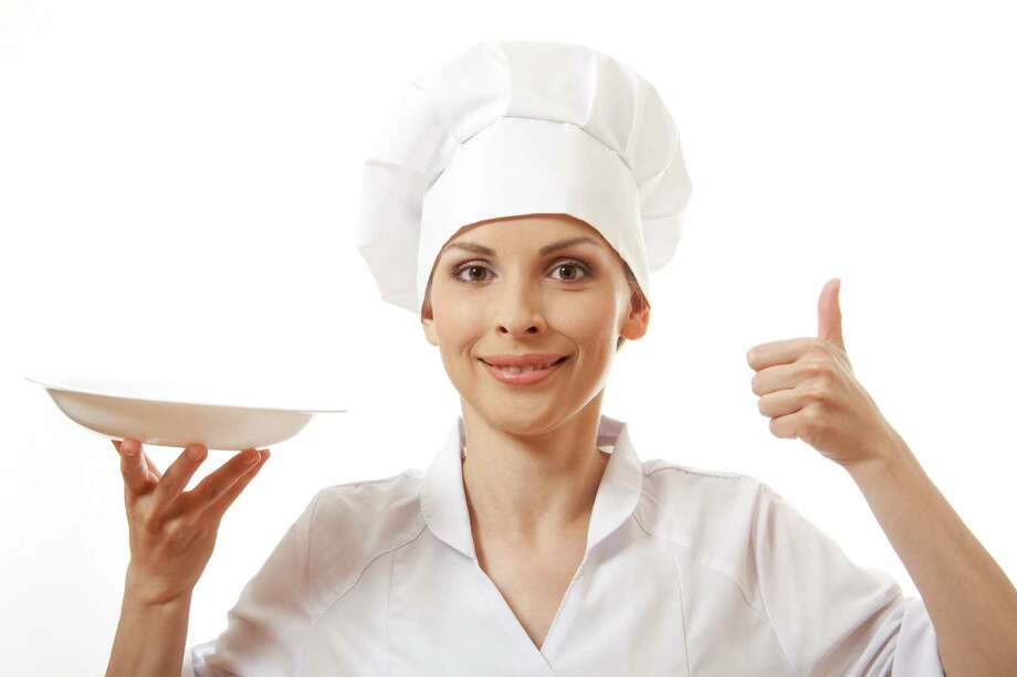 Woman cook holding empty plate, isolated on white / Vasily Merkushev - Fotolia
