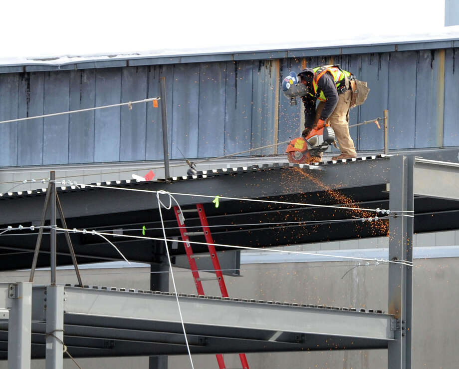A construction worker uses a power saw while working on a section of the steel structure that will become the music instructional space and auditorium at Greenwich High School, Wednesday, Feb. 12, 2104. Photo: Bob Luckey / Greenwich Time
