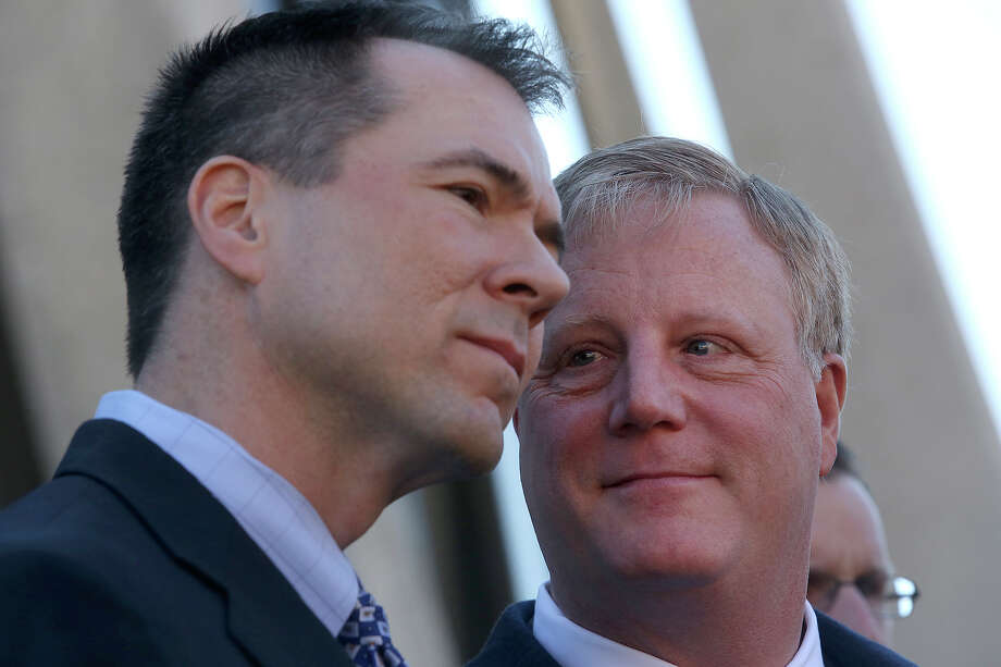Mark Phariss, right, looks at his partner, Victor Holmes, as they stand behind their attorneys as they speak to the media after the hearing for their request for a preliminary injunction to declare Texas' ban on same-sex marriage unconstitutional at the John H. Wood, Jr. U.S. Courthouse in San Antonio on Wednesday, Feb. 12, 2014. Photo: LISA KRANTZ, Lisa Krantz / SAN ANTONIO EXPRESS-NEWS