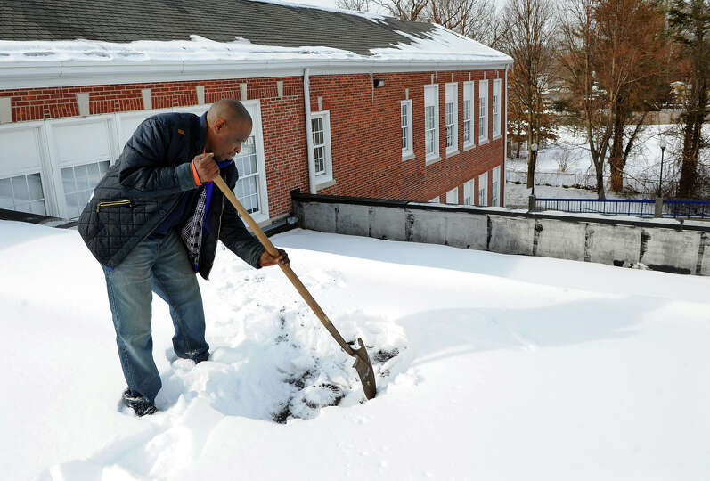 In preparation for Thursday's snow storm, custodian Mike Hooks uncovers a drain pipe on the roof of