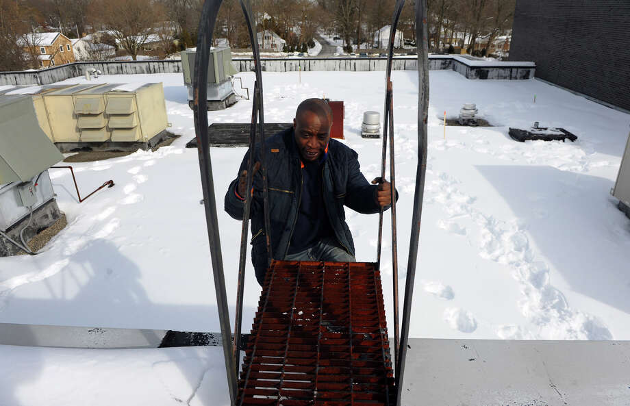 In preparation for Thursday's snow storm, custodian Mike Hooks works up on the roof of Eli Whitney School to remove snow from drains in Stratford, Conn. on Wednesday February 12, 2014. Photo: Christian Abraham / Connecticut Post