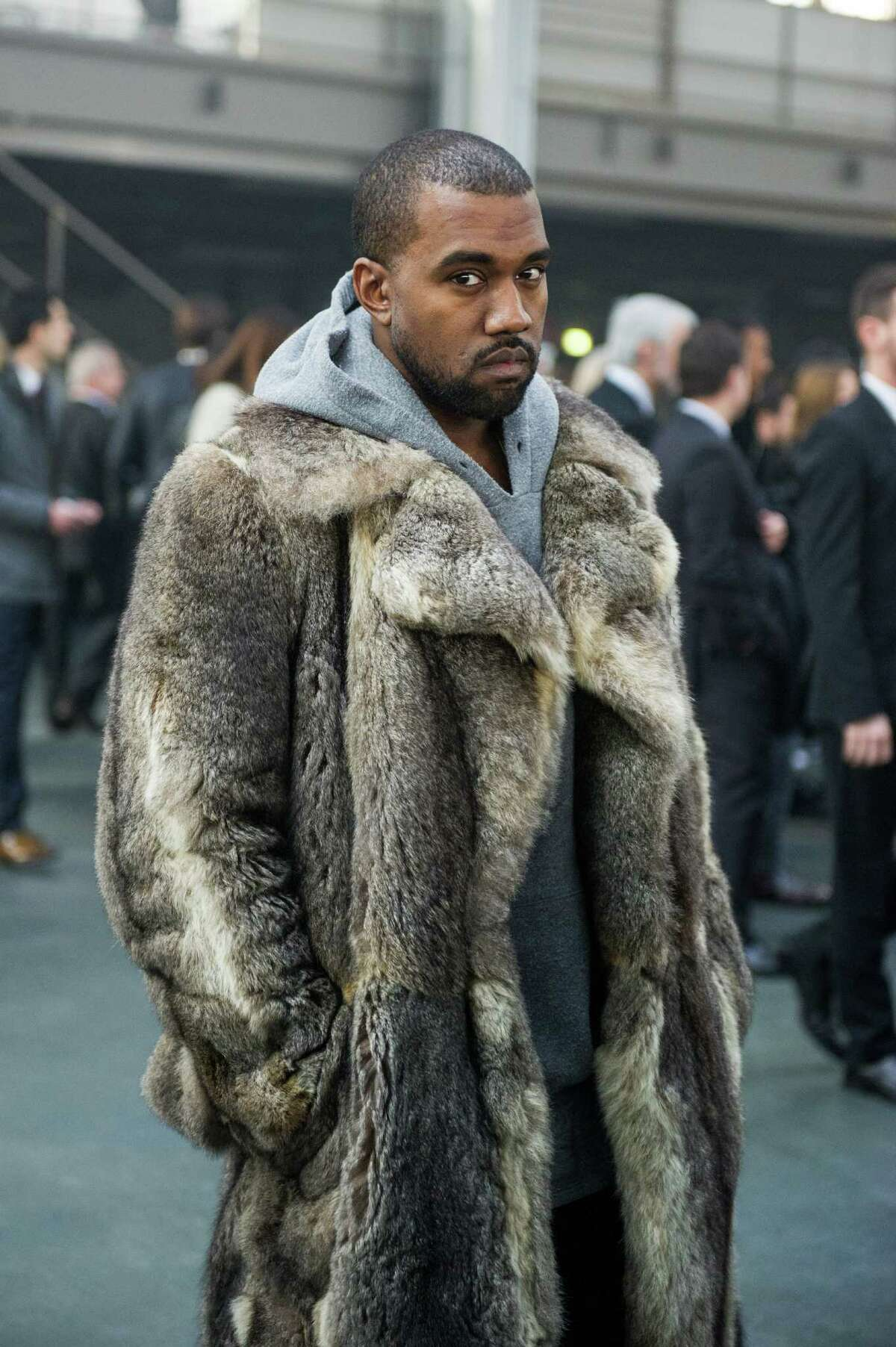 FILE - This Jan. 17, 2014 file photo shows singer Kanye West as he arrives for the Givenchy men's Fall-Winter 2014-2015 fashion collection in Paris. West will not face criminal charges over an incident in which he apparently punched a man in a Beverly Hills chiropractor's office, prosecutors determined Friday, Jan. 31. The Los Angeles County District Attorney's Office rejected a battery case against the rapper because he had reached a civil settlement with the man and there were no significant injuries documented after the altercation. The altercation occurred after the 18-year-old man used a racial slur in an argument with West's fiancee, Kim Kardashian, on Jan. 13, according to a document prepared by a prosecutor. (AP Photo/Zacharie Scheurer, File) ORG XMIT: NYET632