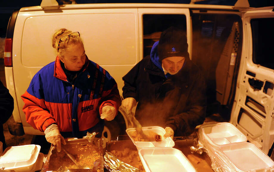Eileen Gillespie and Pete Cook, volunteers from Crossroads Community Church, in Trumbull, serve food to people at the P.T. Barnum apartment complex as part of the weekly visit that Bridgeport Rescue Mission makes in Bridgeport, Conn. on Tuesday February 11, 2014. One of the Bridgeport Rescue Mission's two mobile kitchens has broken down beyond a reasonable cost to repair, forcing the Mission to use this cargo van to transport and distribute meals in the area's most impoverished neighborhoods. But the meals are cold by the time they're served. The Mission is looking for another used food truck outfitted for delivering hot meals. Photo: Christian Abraham / Connecticut Post