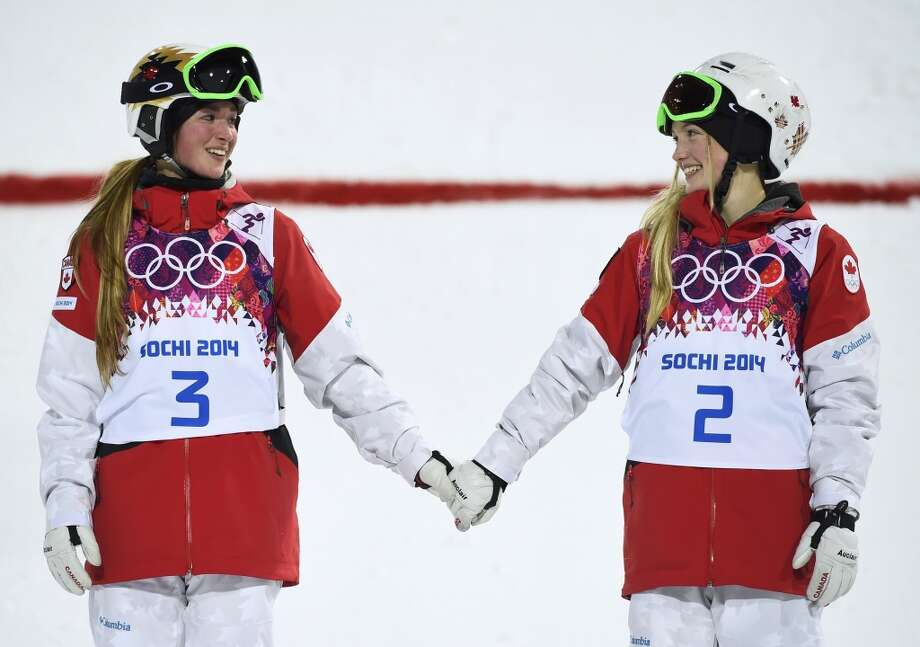 Second-placed Chloe Dufour-Lapointe (L) of Canada and her sister, first-placed Justine Dufour-Lapointe (R), hold hands during the flower ceremony for the women's freestyle skiing moguls event at the Sochi 2014 Winter Olympics in Rosa Khutor, February 8, 2014.        REUTERS/Dylan Martinez Photo: DYLAN MARTINEZ, Reuters