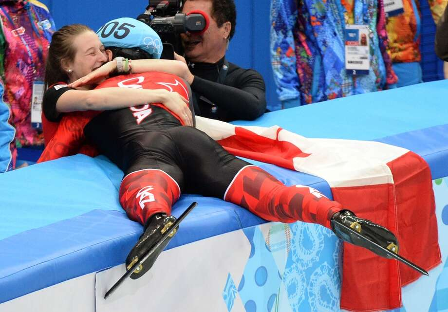 Canada's Charles Hamelin (R) embraces his girlfriend Marianne St-Gelais after winning the gold medal in the Men's Short Track 1500 m Final at the Iceberg Skating Palace during the Sochi Winter Olympics on February 10, 2014.  DAMIEN MEYER/AFP/Getty Images Photo: DAMIEN MEYER, AFP/Getty Images