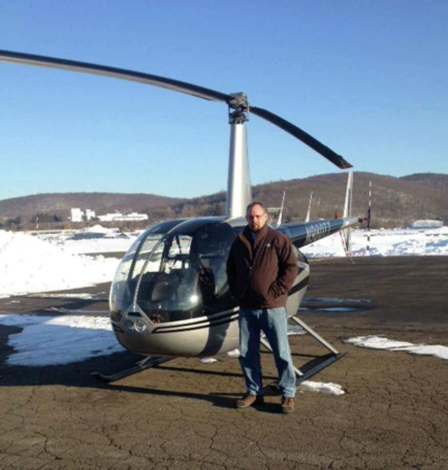 Chris Siburn, recently fired from his job as a deer warden in Redding, Conn., stands next to a helicopter that he used in order to count deer from the air. Photo: Contributed Photo / The News-Times Contributed