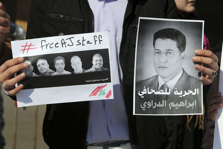 A protester in Beirut holds photos of Al Jazeera journalists detained in Egypt on criminal charges for contacting the Muslim Brotherhood. Photo: Hasan Shaaban, Reuters