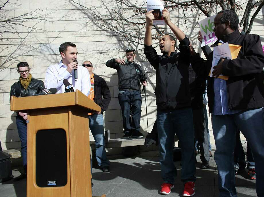 John Zimmer, co-founder of ride-sharing service Lyft, tries to speak as for hire taxi cab drivers Wale Balcha, left, and Samatar Guled shout questions about insurance during a rally to support ride-sharing services in Seattle on Wednesday, February 12, 2014. The Seattle City Council is considering regulations for the companies and drivers that provide the service. Photo: JOSHUA TRUJILLO, SEATTLEPI.COM / SEATTLEPI.COM