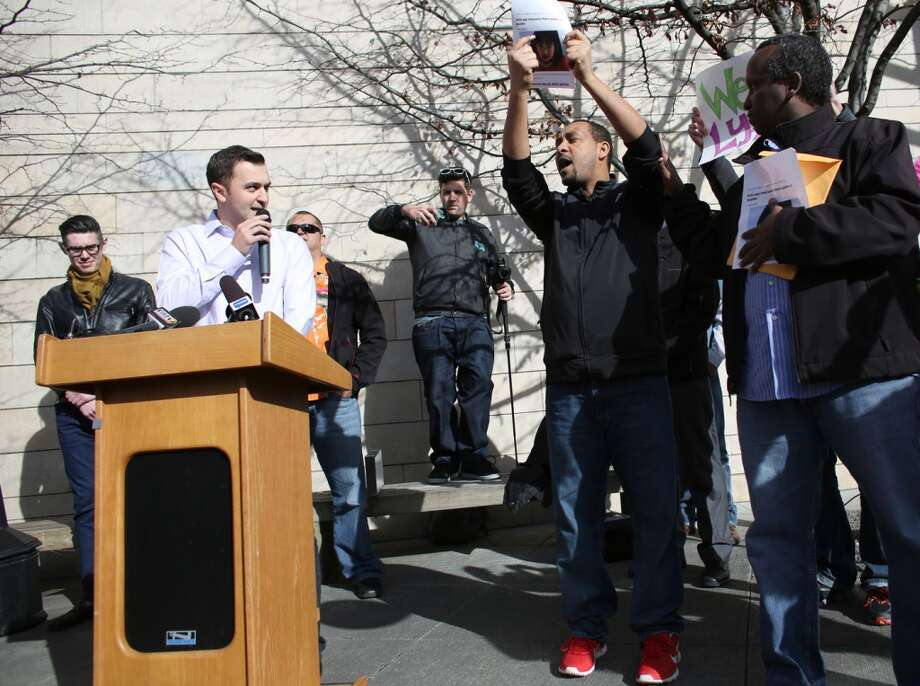John Zimmer, co-founder of ride-sharing service Lyft, tries to speak as for hire taxi cab drivers Wale Balcha, left, and Samatar Guled shout questions about insurance during a rally to support ride-sharing services in Seattle on Tuesday, February 12, 2014. The Seattle City Council is considering regulations for the companies and drivers that provide the service. (Joshua Trujillo, seattlepi.com) Photo: JOSHUA TRUJILLO, SEATTLEPI.COM