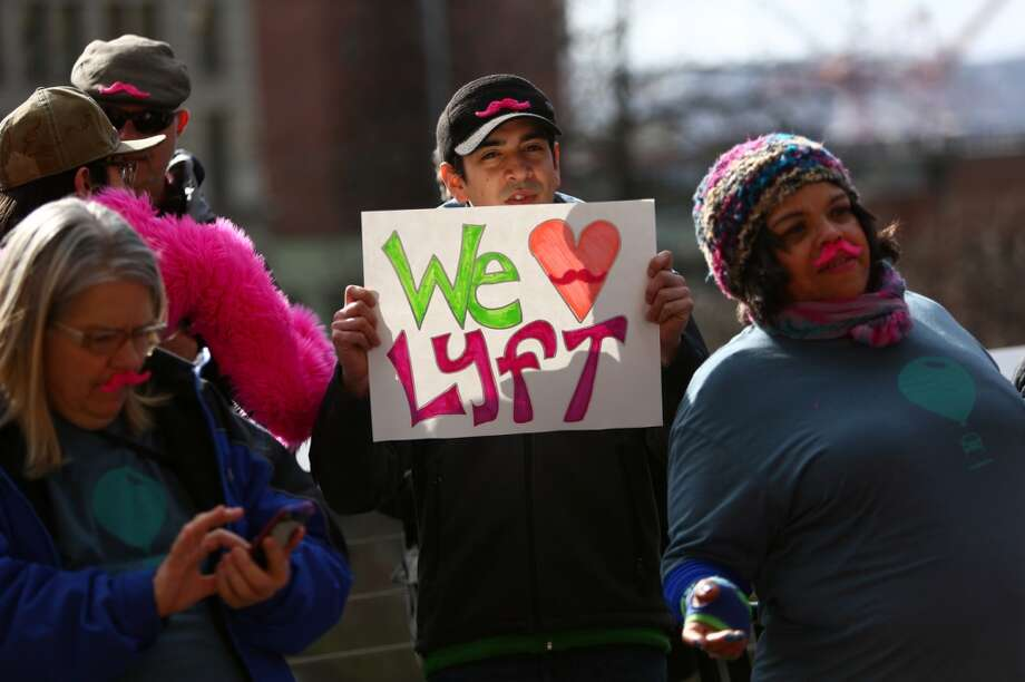 People gather during a rally to support ride-sharing services in Seattle on Tuesday, February 12, 2014. The Seattle City Council is considering regulations for the companies and drivers that provide the service. (Joshua Trujillo, seattlepi.com) Photo: JOSHUA TRUJILLO, SEATTLEPI.COM