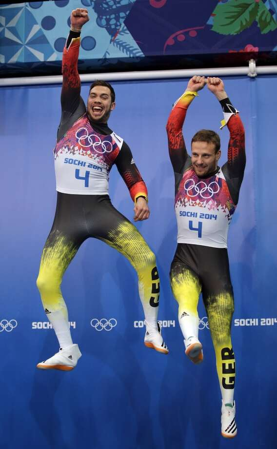 The doubles team of Tobias Wendl and Tobias Arlt from Germany jump onto the podium for the flower ceremony after they won the gold medal during the men's doubles luge at the 2014 Winter Olympics, Wednesday, Feb. 12, 2014, in Krasnaya Polyana, Russia.(AP Photo/Jae C. Hong) Photo: Jae C. Hong, Associated Press