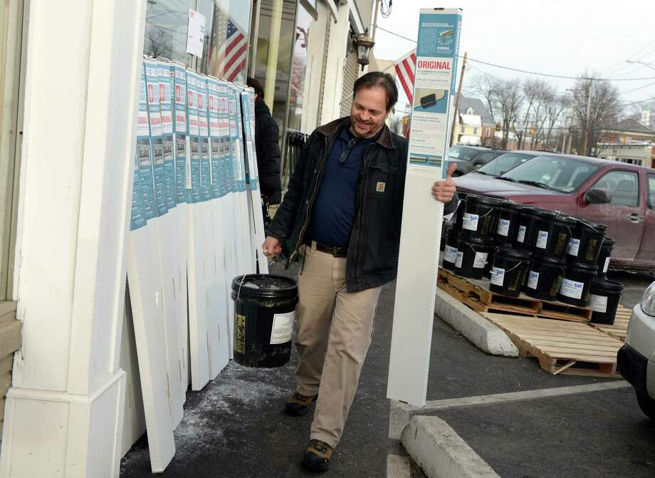 Jay Washburn, of Fairfield, buys a bucket of salt and a roof rake ahead of the approaching storm Wednesday, Feb. 12, 2014 at Hemlock Hardware on the Post Road in Fairfield, Conn. Photo: Autumn Driscoll / Connecticut Post