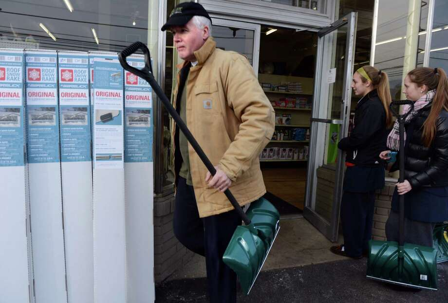 Jack Griffin, of Fairfield, leaves Hemlock Hardware after picking up a shovel Wednesday, Feb. 12, 2014, as Maggie Salandra, 16, and Sophie Benedetti, 17, of Fairfield, head into the store to buy a shovel. Photo: Autumn Driscoll / Connecticut Post