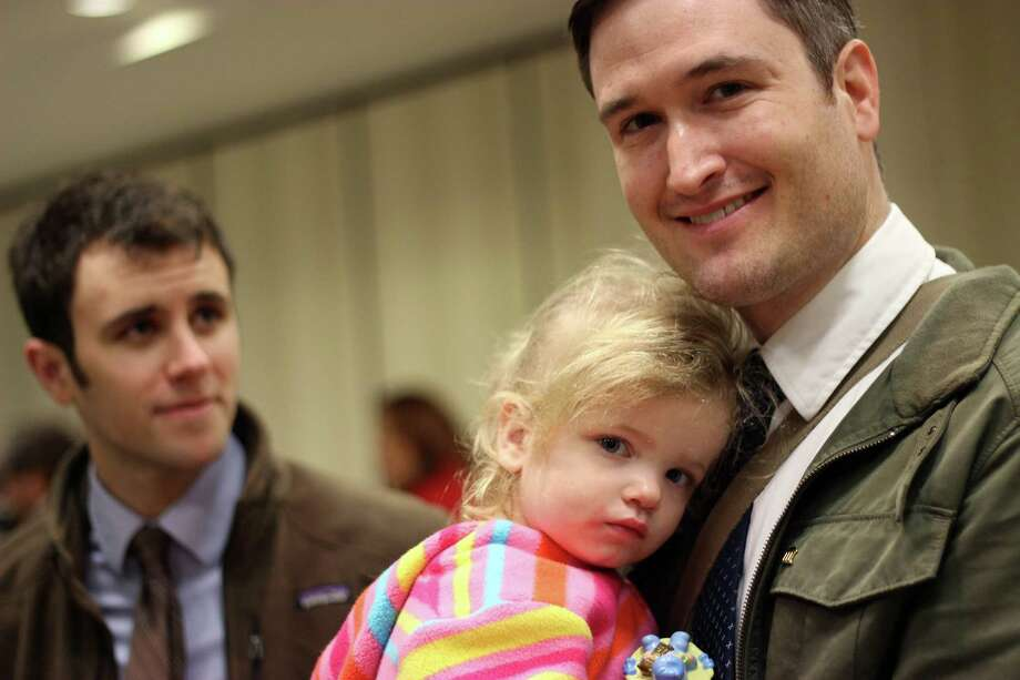 FILE - Nicholas J. Van Sickels, right, stands with his husband, Andrew S. Bond, and holds their adopted daughter, Jules, 2, before a news conference in New Orleans about a federal lawsuit filed Wednesday, Feb. 12, 2014, to challenge the Louisiana Constitution's ban on recognizing same-sex marriages performed in states where they are legal. They are among four couples, all married states where same-sex marriage is legal, who joined the Forum for Equality Louisiana in a suit against the state registrar and state revenue secretary. (AP Photo/Janet McConnaughey) Photo: Janet McConnaughey, STF / AP
