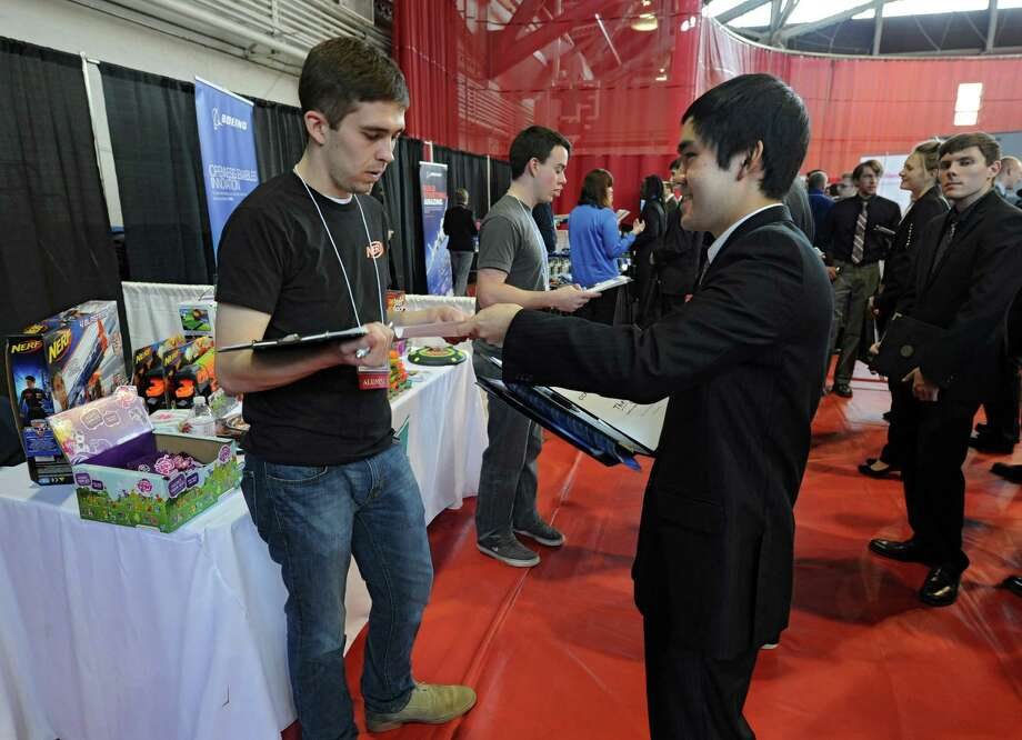 Sophomore Freddy Wang, 19, of Clifton Park, right, hands his resume to Hasbro representative and alumnus Jacob Borowiec during the annual Spring Career Fair hosted by The Center for Career and Professional Development (CCPD ) Wednesday, Feb. 12, 2014, at the RPI Armory in Troy, N.Y.  (Lori Van Buren / Times Union) Photo: Lori Van Buren / 00025737A