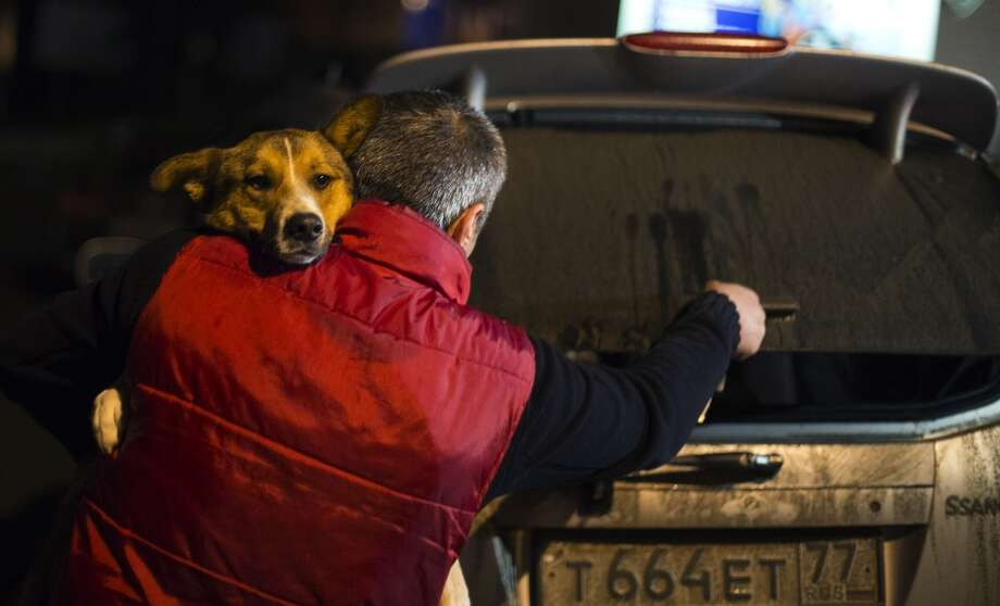 Animal activist Igor Airapetian carries a stray dog to his car brought out of Sochi by fellow activist at a rendezvous point 120 kilometers away from the Olympic area in the early morning hours of Tuesday, Feb. 11, 2014, in Tuapse, Russia. Airapetian is one of a dozen people in the emerging movement of animal activists in Sochi alarmed by reports that the city has contracted the killing of thousands of stray dogs before and during the Olympic Games. Stray dogs are a common sight on the streets of Russian cities, but with massive construction in the area the street dog population in Sochi and the Olympic park has soared. Useful as noisy, guard dogs, workers feed them to keep them nearby and protect buildings. They soon lose their value and become strays. Tonight, a few dogs will be taken on their way to a new life in Moscow. (AP Photo/David Goldman) Photo: David Goldman, Associated Press