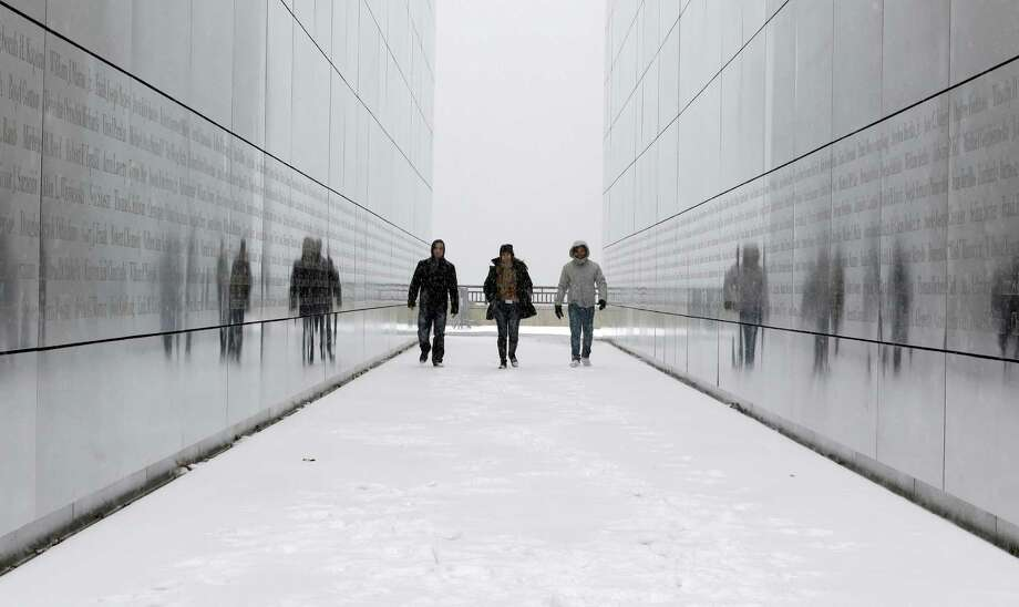 FILE - In this Tuesday, Jan. 21, 2014 file photo, tourists walk through the snow-covered Empty Sky Memorial at Liberty State Park in Jersey City, N.J. Researchers who analyzed local climate trends and hospital records on millions of Americans say there may be a link between weather and the risk for stroke. Cold weather, high humidity and big daily temperature swings brought more stroke hospitalizations. The study by researchers from Yale, Harvard and Duke universities was discussed Wednesday, Feb. 12, 2014 at a stroke conference in San Diego. (AP Photo/Julio Cortez) ORG XMIT: NY945 Photo: Julio Cortez / AP