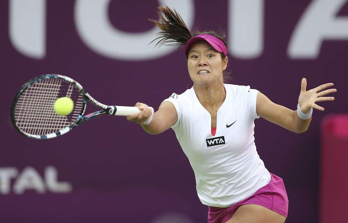 Li Na of China hits a return to Magdalena Rybarikova of Slovakia during their Qatar Open women's tennis match in Doha February 12, 2014. REUTERS/Fadi Al-Assaad (QATAR - Tags: SPORT TENNIS)