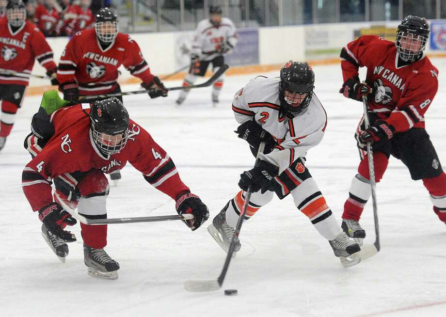 Ridgefield's Brendan Winne (2) gets past New Canaan defenders John McMahon (4) and Drew Morris (8) in Ridgefield's 5-4 win over New Canaan in the high school boys hockey game at the Winter Garden Arena in Ridgefield, Conn. on Wednesday, Feb. 12, 2014. Photo: Tyler Sizemore / The News-Times