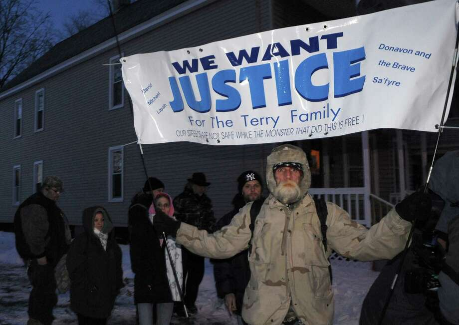 John Taylor holds a banner during a rally for justice on Wednesday Feb. 12, 2014 in Schenectady, N.Y. Days after federal prosecutors dropped charges against a local man accused of setting a fire that killed David Terry, 32, and his children, Layah Terry, 3; Michael Terry, 2; and Donavan Duell, 11 months, relatives held a rally to call for justice in the case. (Michael P. Farrell/Times Union) Photo: Michael P. Farrell / 00025734A