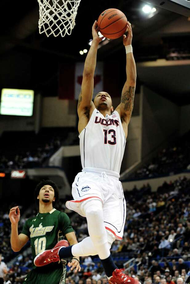 Connecticut's Shabazz Napier (13) scores a basket as South Florida's Josh Heath, left, defends during the first half of an NCAA college basketball game on Wednesday, Feb. 12, 2014, in Hartford, Conn. (AP Photo/Jessica Hill) Photo: Jessica Hill, Associated Press / Associated Press