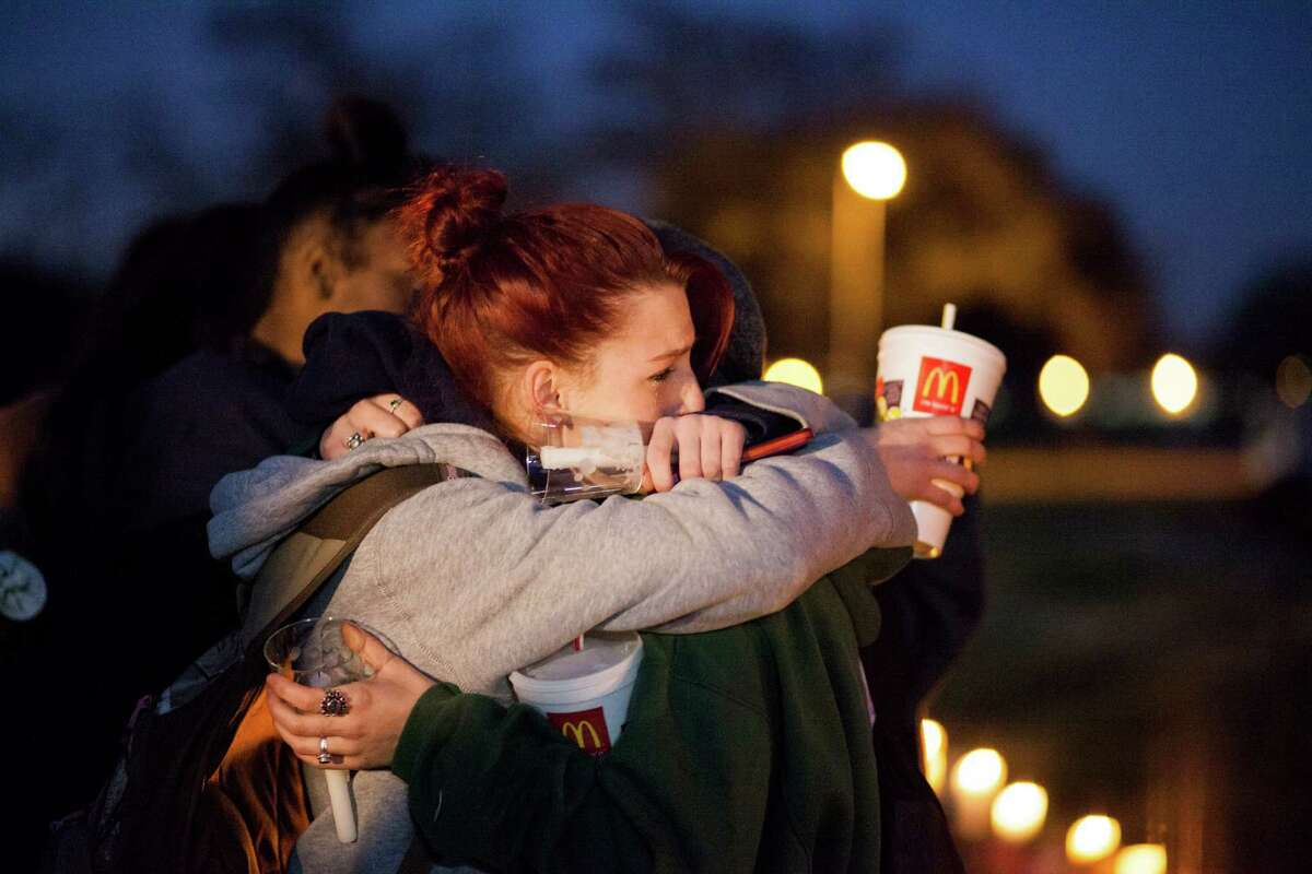Ashlee Brown, 15, left, and Reagan Deschenes, 18, embrace at a vigil in Clear Lake for Corriann Cervantes. Officers say Cervantes was sexually assaulted and killed by two boys in a satanic ritual on Feb. 5.