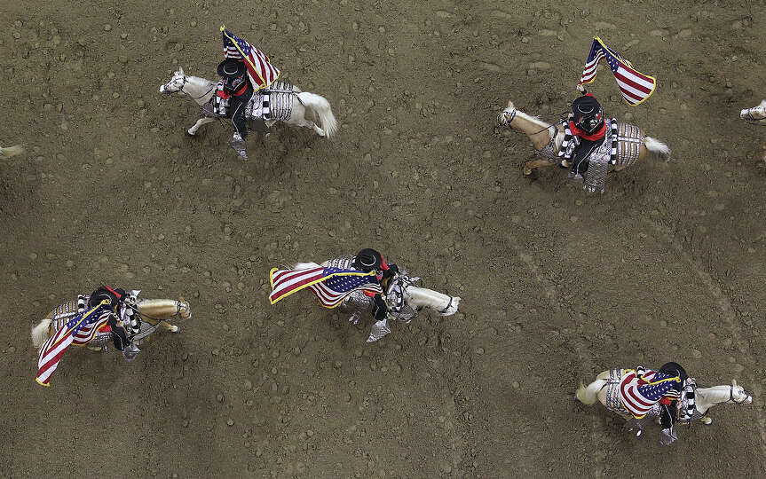U.S. flags abound during the Grand Entry at the start of the San Antonio Stock Show Rodeo at the AT&